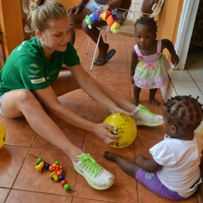 A volunteer working with children at a Summer Camp in Jamaica, leads a ball activity at her placement.